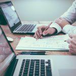 Management fee ou transaction fee? Vamos falar sobre isso? Imagem de duas pessoas sentadas lado a lado, com foto nos computadores a sua frente, utilizada para ilustrar o artigo que fala sobre a importancia do debate sobre os tipos de contratos de prestação de serviços das TMCs.